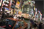 Japan, Tokyo, Shinjuku Ward, busy street scene and neon signs at night