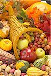 Corne d'abondance avec citrouilles, courges, maïs, pommes, raisins et feuilles