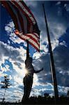 Il s'agit d'un garde-parc, hissant le drapeau américain sur son mât. Il se détache, bras atteindre contre un ciel bleu avec des nuages.