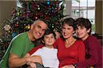 Parents avec enfants (8-14) de l'arbre de Noël dans la maison, sourire, portrait