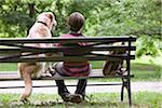 Junge und Hund sitzt auf der Parkbank