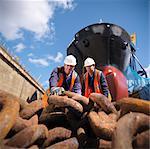Travailleurs en examinant la chaîne au chantier naval