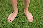 Gros plan du pieds nus de garçon sur l'herbe, Alpes, France