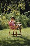 Boy (5-7) sitting on chair in garden