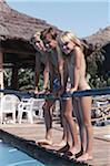 Three children (4-9) standing by poolside