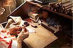 Senior woman making cigars in cigar factory, rear view