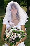 Junge Braut mit Schleier über das Gesicht, hält blumenstrauss, Lächeln, Porträt