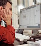 Männlichen Büroangestellten am Schreibtisch, starrte auf den Computer, das Gesicht in den Händen