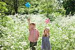 Kinder spielen mit Windräder im Bereich der Blumen