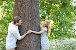 Couple holding hands around tree