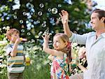 Famille jouant avec des bulles dans le parc