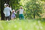 Famille marchant main dans la main dans le parc