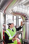 Homme d'affaires vérification des jauges sur tuyaux en usine