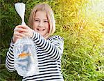 Girl carrying goldfish in plastic bag