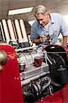 Senior man looking at car engine in automobile repair shop