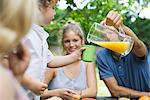 Famille ensemble en plein air, verser le verre de jus pour fils de père