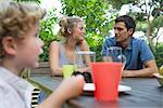 Famille de détente ensemble à table à l'extérieur