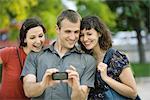 Homme lui-même photographier avec deux amis à l'aide de téléphone portable
