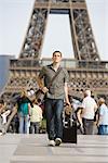 Mâle touristique à pied avec bagages, Tour Eiffel, Paris, France