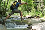 Man jumping over stream through woods