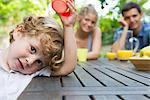 Petit garçon reposant à la table de pique-nique avec les parents