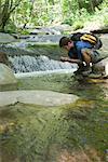 Homme accroupi par flux, interception d'eau dans les mains