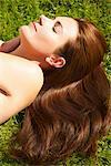 Frau mit langen gewellten Haar liegend auf Gras, Detailansicht