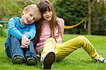 Boy and Girl Sitting on Lawn