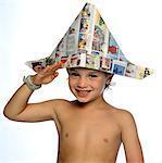 Boy Wearing Newspaper Hat Saluting