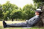 Homme d'affaires, faire la sieste sur l'arbre dans le parc