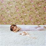 Mädchen (3-5) auf Bauch liegend, Ballettschuhe, Porträt, Seitenansicht