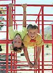 Deux garçons (9-11) suspendues sur les barres dans l'aire de jeux, sourire, portrait