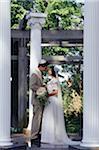 Bride and groom standing among Ionic columns