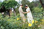 Bride and groom standing in park, side view, defocused