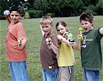Enfants (9-12) dans le parc qui vise pistolets et l'eau de bombes, portrait