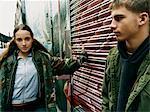 Teenage Boy et Girl With Attitude debout dans une ruelle se penchant sur un volet roulant