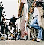 Moyenne groupe d'adolescents dans une ruelle de dos regardant Stunts sur une planche à roulettes