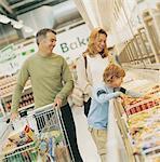 Familie von drei mit einem Einkaufstrolley Abschnitt Tiefkühlkost eines Supermarktes betrachten