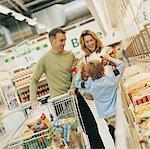 Kind zeigt seine übergeordneten Taschen Tiefkühlkost in einem Supermarkt