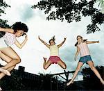 Mid Air Shot de trois jeunes filles sautant
