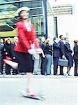Femme dans une veste rouge à cheval devant une file de personnes sur un Scooter de Push