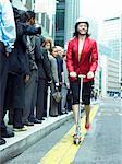 Femme d'affaires dans une veste rouge cheval passé de personnes en ligne sur un Scooter de Push