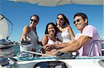 Vierköpfige Familie auf einem Boot, Man zieht ein Seil