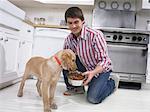 Homme donnant son chien un bol de nourriture