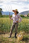 Farmer Holding Pitchfork on Organic Farm
