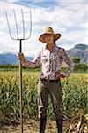 Portrait of Farmer Holding Pitchfork on Organic Farm