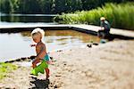 Girl running beside lake in sun
