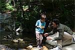 Père et fils, exploration de la nature, garçon tenant roche