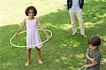 Mädchen spielen mit Kunststoff Reifen im Freien, Lächeln in die Kamera