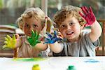Kleine Mädchen und der junge zeigt Hände fallen in Farbe, Porträt